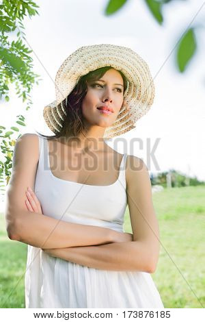 Thoughtful young woman in sundress and hat standing arms crossed in park