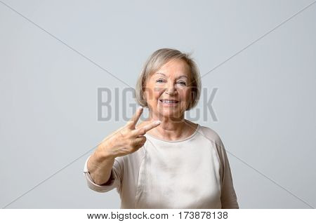 Senior woman showing V sign with two fingers as victory gesture looking at camera with confident happy face standing against plain grey background