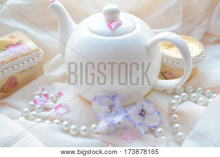 white kettle , beads, vintage jewelry boxes and flowers on a cream background