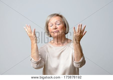 Senior Woman With Her Hands Up To The Sky