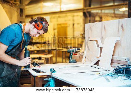 Professional cabinetmaker grinding wooden workpiece