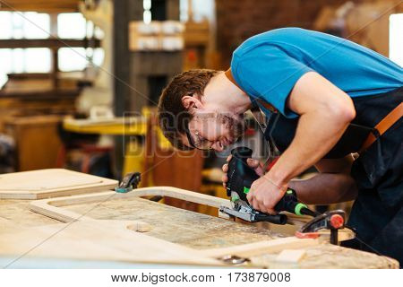 Carpenter using power-tool for cutting wood