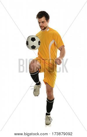 Young soccer player bouncing ball on knee isolated over white background