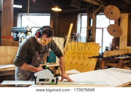 Man in protective eyeglasses and headphones cutting wooden plank on workbench
