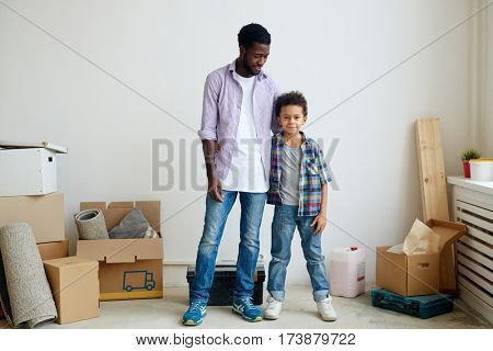 Affectionate father and son looking at camera in new flat