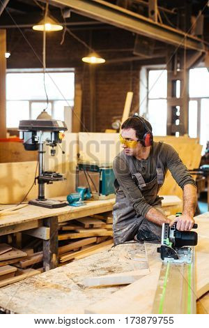 Young craftsman using power-tool while working