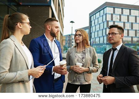 Young employees discussing their plans in urban environment