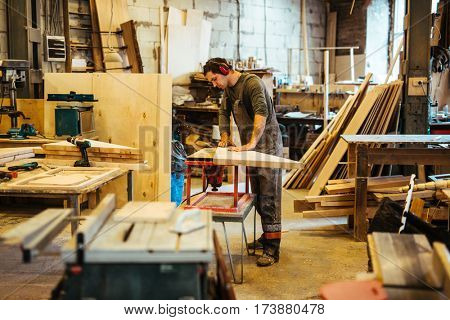 Woodworker by workbench looking at wooden plank