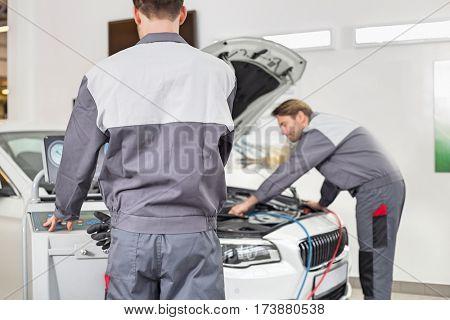 Male maintenance engineers examining car in workshop