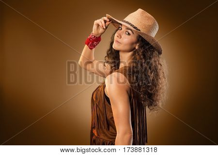 The cowgirl fashion woman over a brown studio background