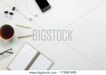 Top view accessories office desk concept.mobile phone coffee notepaper pencil earphones on office desk.
