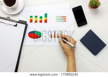 Top view accessories business office desk with businessman.Businessman working with colorful chared mobile phone coffee notebook cactus clipboard on white office desk with copy space.