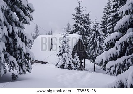 Old Shelter In The Winter Mountains. Smoke Comes From The Chimney