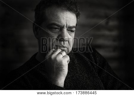 Hard day. Black and white vintage style portrait of a sad man. Low key.
