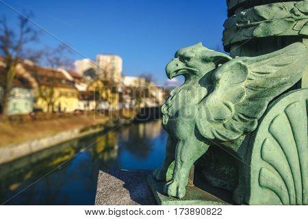 LJUBLJANA SLOVENIA - FEBRUARY 19 2017: Statue on Dragon Bridge over Ljubljanica river in Ljubljana capital of Slovenia. It was originally named The Jubilee Bridge of the Emperor Franz Josef I.
