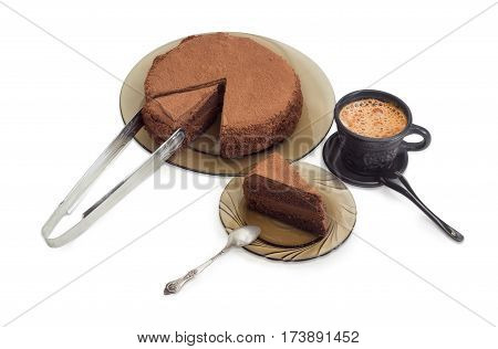 Partly sliced round chocolate cake sprinkled with cocoa powder on a glass dish and kitchen tongs piece of the cake with spoon on the glass saucer and coffee with milk in black ceramic cup on a light background