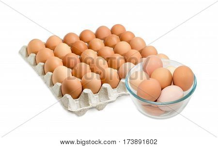 Brown chicken eggs in the glass bowl and in the cardboard egg tray with rooms for thirty eggs on a light background