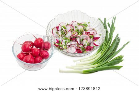 Vegetable salad of the fresh sliced red radish green onion in transparent glass salad bowl and separately whole red radish in glass bowl and bundle of the green onion on a light background