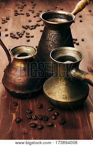 Hot coffee in group shabby antique turkish pots cezve with crema beans with blur on brown old wooden board background vertical shot. Rustic style.