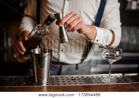 Barman in shirt is making alcohol coctail no face close up