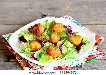 Golden fried mashed potato balls on a plate. Crispy fried balls made from mashed potatoes with pumpkin seeds served with salad leaves mix and basil. Rustic style. Closeup