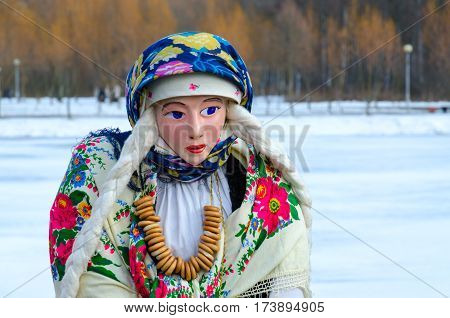 Shrovetide doll in colorful shawls shirt and fur sleeveless jacket with bunch of bagels on neck