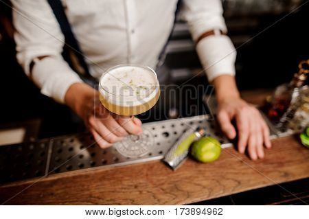 close up barmans hands with coctail on the bar stand no face