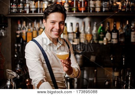 smiling barman holding a coctail at the bar stand