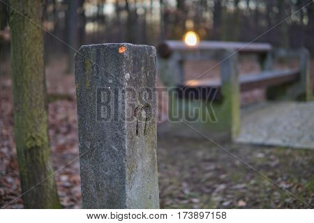 Traditional old milestone with a carved number seventeen with a sunset background as a symbol of path, progress and achievement