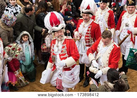 uniformed foot group in red-white in the carnival procession in Cologne - Participants of the rose monday parade in cologne on February 27, 2017