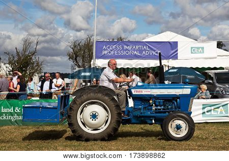 WEEDON, UK - SEPTEMBER 1: A vintage field tractor is driven around the main show arena for the public to view at the Bucks County Show on September 1, 2016 in Weedon