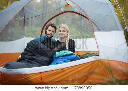 Young Couple With Sleeping Bags In Tent