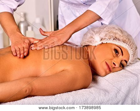 Massage woman therapist making manual therapy back. Hands of masseuse close up. Treatment of spinal injuries 40 old client in spa salon. Patient in medical hat. Young beautician on foreground.