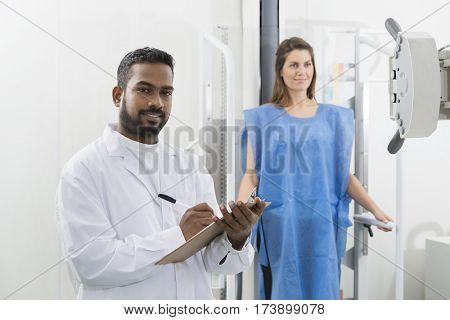 Portrait Of Male Radiologist Writing On Clipboard In Hospital