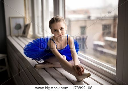 Child girl in a pink tutu dancing in a room.