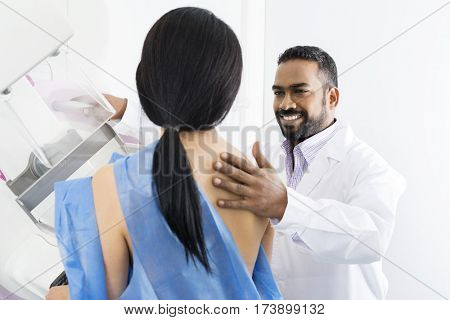 Male Doctor Assisting Woman Undergoing Mammogram X-ray Test