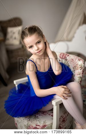 little ballerina sitting on a chair. A girl in a blue ballet tutu dancing in a room. The girl is a ballerina.