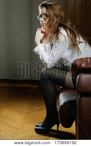The Girl In Glass And Stockings Sits On A Sofa