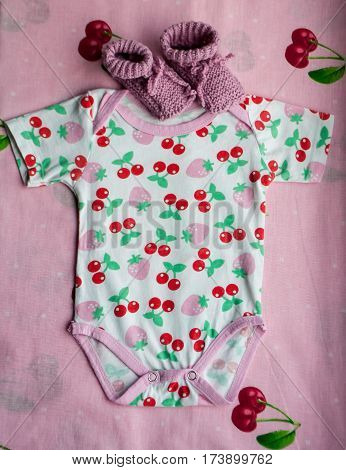 Clothes for newborns with cherries and baby's pink bootees on the bedclothes with cherries