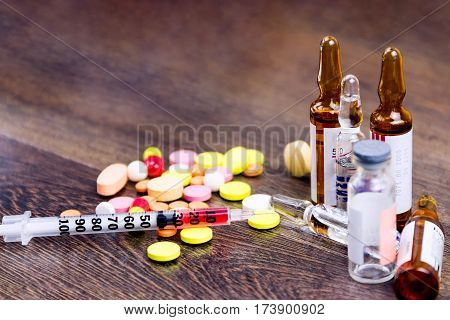 Pills, Injector And Ampules Isolated On Wooden Background
