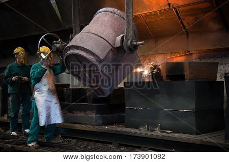 Workers with helmet working hard inside a foundry