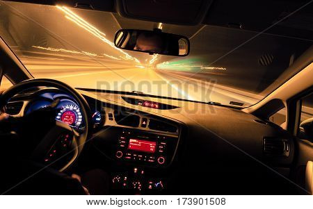 Night driving view from inside car city and other cars light is motion blurred.