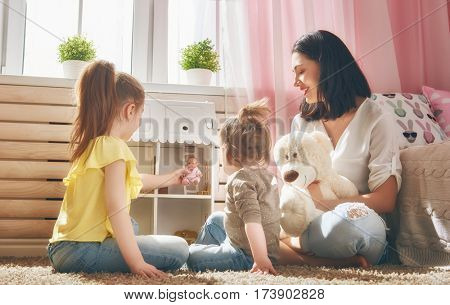 Happy mother and daughters girls play with doll house at home. Funny lovely family are having fun in kids room.