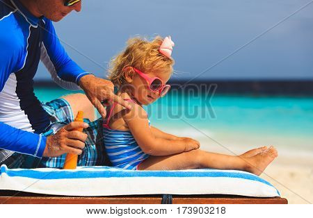 father applying sunblock cream on daughters shoulder at beach