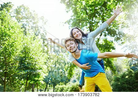 Happy couple on vacation. Lovers are laughing. Happy guy and girl. Lovers enjoy each other in the evening park.