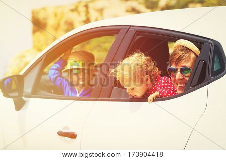 happy mother with little son and daugther travel by car
