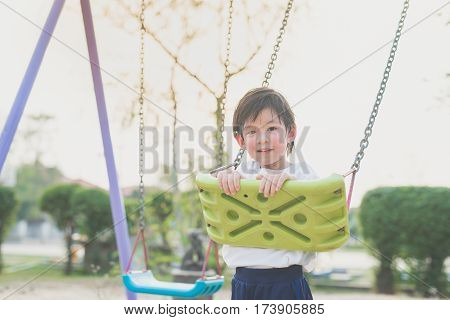 Cute Asian child playing on swing in the park