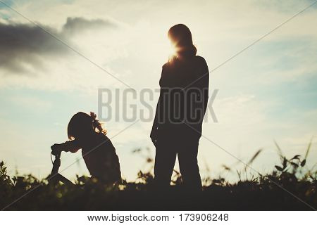 mother teaching little daughter to ride bike in sunset nature