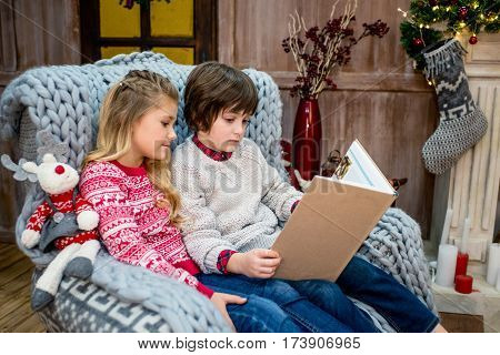 Engrossed children sitting on grey armchair and reading book