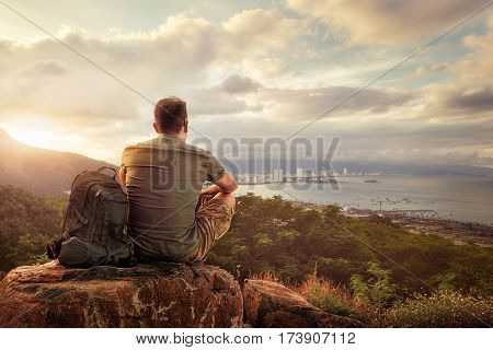 Traveller with backpack sitting on top of mountain enjoying view coast a modern city Vietnam Nha Trang. Traveling along mountains and coast freedom and active lifestyle concept